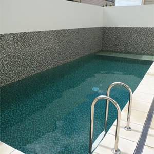 GCR270 Camo Light 23mm glass mosaic tiles shown tiling a feature wall as well as the pool interior